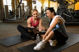 Adult female with personal trainer at gym.