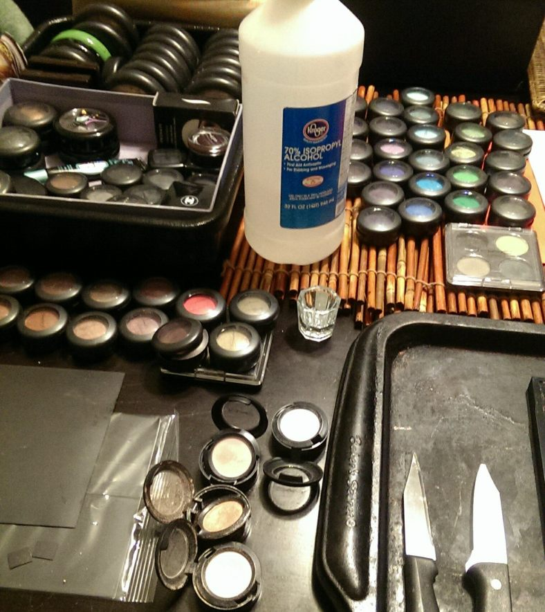 Here was my setup for the MAC eye shadow depotting session I had.  The larger pots in the top left of the image are my MAC Mineralized Skinfinishes.  The other pots and small palettes comprise only about half of my MAC eye shadow collection.  The knives, cookie sheet, rubbing alcohol, and magnet sheets you see in the image were used in the depotting process.